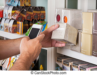Cropped image of man's hand scanning product through mobile phone