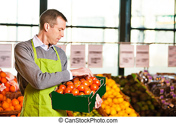 Market assistant wearing apron with holding box of tomatoes in the supermarket