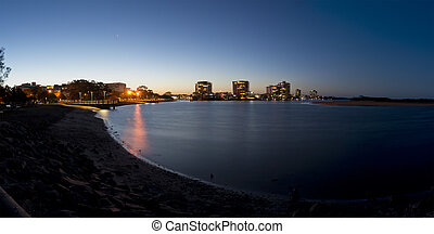 Panoramic image of Maroochydore at twilight just after sunset. Image taken from Cotton tree showing Maroochy river in freground and midground with river bank, park and jetty on one side and sandy island on the other side. Maroochydore CBD with highrise buildings with lights on at the background and ...