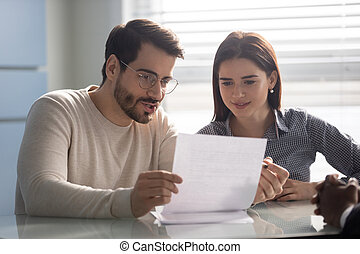 Married couple reading carefully contract terms of conditions.