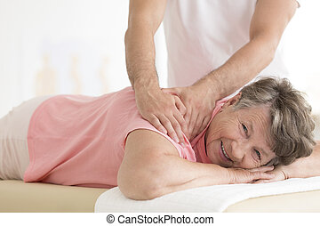 Masseur setting elderly woman shoulder