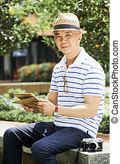 Mature Chinese man resting in park