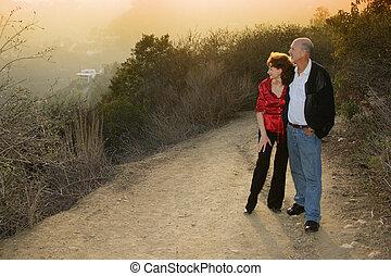 Mature couple enjoying sunset on a trail outdoors.