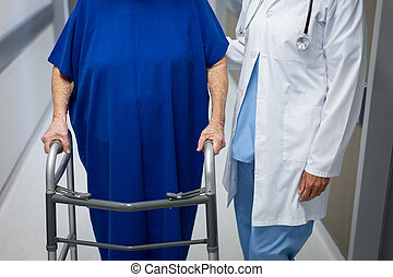 Mature female doctor and senior female patient together in clinic