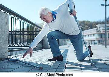 Mature man gathering his crutch up after falling down