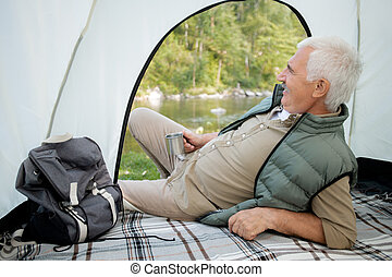 Mature restful man with hot tea lying in tent while looking at river