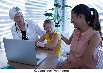 Matured female doctor and mother talking with girl patient in clinic