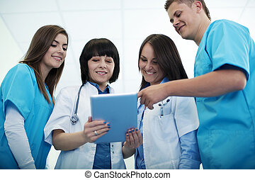Medical team checking results on digital tablet