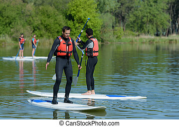 men on a stand up paddle board