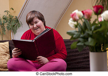 Mentally disabled woman is reading a book and smiles