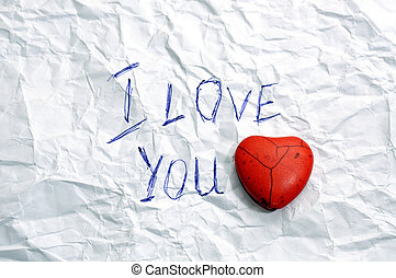 message I Love You on wrinkled paper and red heart