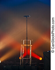 A microphone on stage in lights.