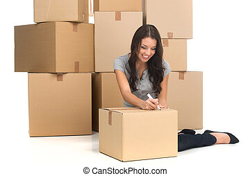 mid adult happy woman during move with boxes at new flat. young woman writing on boxes and smiling while moving to new apartment