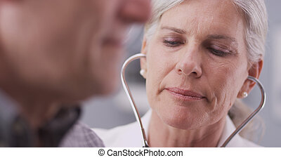 Mid-aged doctor listening to heart