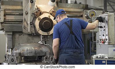 Milling machine operator working in factory workshop. Cutter cuts metal workpiece. shavings twisted into spiral. Metal working milling machine. Produces metal detail in factory.