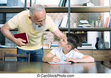Mindful grandparent helping kid with home assignment