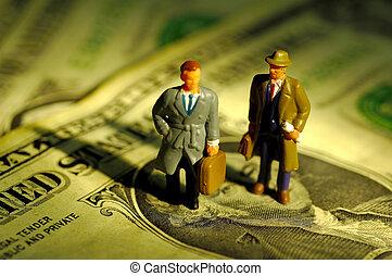 Miniature Businessmen Standing on Money.