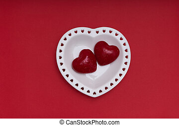 Mockup Valentines day. White plate in the shape of a heart on red background Copy space.