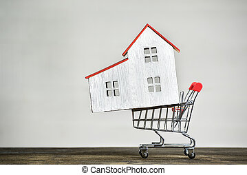 Model house and shopping cart. Buying home concept. Mortgage rent.