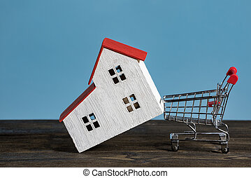 Model house and shopping cart on a blue background. Buying home, mortgage concept