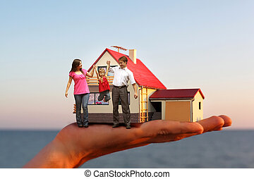 model of house with garage on hand against sea and family with girl collage