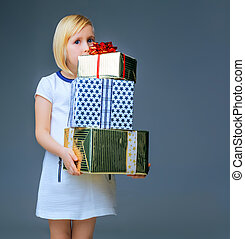 modern child on grey holding pile of christmas present boxes