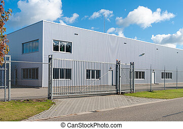 modern exterior of an industrial building, surrounded by a fence with iron gate