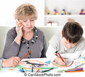 modern grandparents visiting grandson sitting at the table in the nursery. concept of education