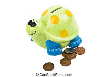 Money box tortoise with UK coins isolated on white background