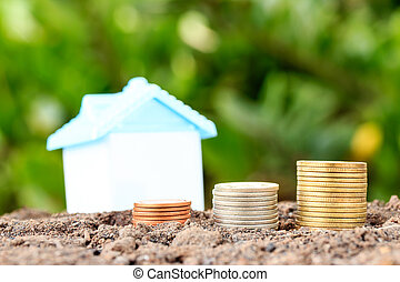 Money growth concept coins in soil .Collect money to build a house.