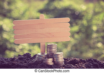 Money growth concept coins in soil with filter effect retro vintage style