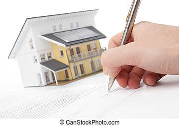 Man confirm mortgage contract (estate agency client sign contract). Model of the active (energy positive) house in background out of focus.