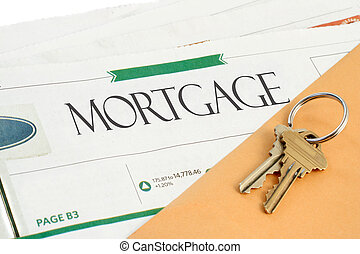 conceptual mortgage section of the newspaper with yellow envelope, and keys