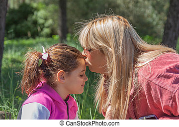 mother affectionately kissing her daughter on her forehead