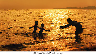 Mother and children playing on the beach