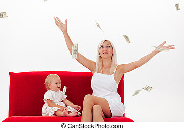 Mother and daughter in white clothes sit on a red sofa in the rain of dollars