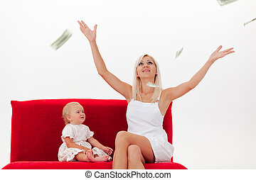 Mother and little daughter sit on a red sofa in the rain of dollars