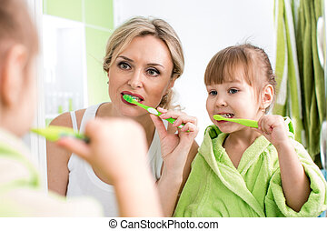 mother with child brushing teeth