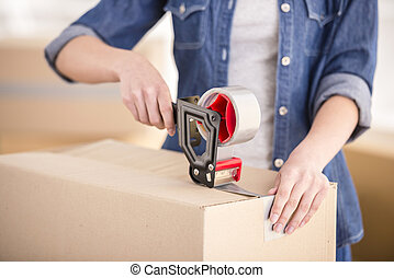 The young happy woman packing boxes. Moving, purchase of new habitation.