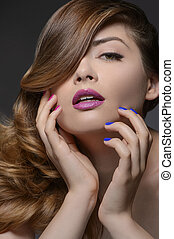 Multi colored nails. Portrait of beautiful women touching face with her hands while isolated on black