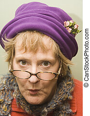Beauitful older woman with a fun expression wearing a purple hat and red sweater.