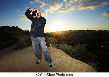 Nature photographer taking photo at sunset