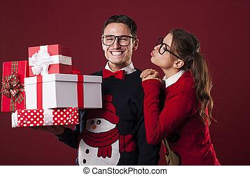 Nerdy woman kissing her boyfriend in christmas time
