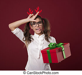 Nerdy woman with christmas gift showing loser sign