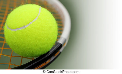 New tennis ball on a new racket with orange string(gut) and the green hard court surface blurred in the background. The photo has copy space for text on the right.