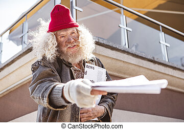 Nice aged man holding newspapers