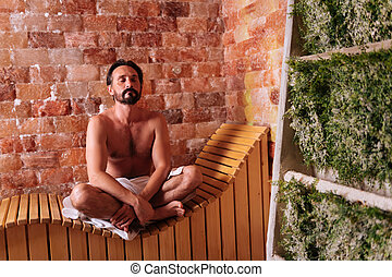 Nice bearded man trying to relax in sauna