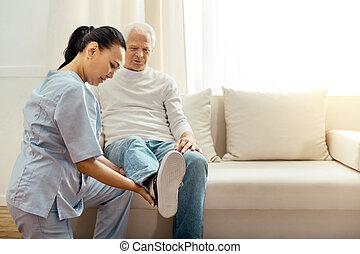 Nice elderly man holding his leg up