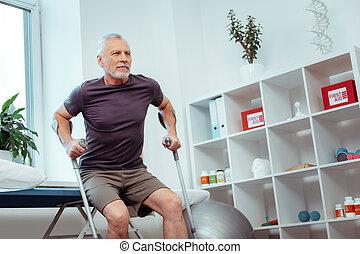 Nice elderly man preparing to get up