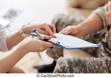 Psychological test. Close up of a sheet of paper being given to a nice military man while having an appointment with a psychologist